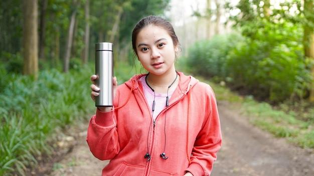 Acqua potabile della donna asiatica dopo l'esercizio dalla foresta verde della natura