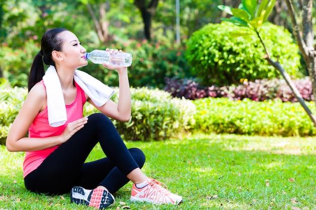 Acqua potabile della donna asiatica dopo lo sport nel parco