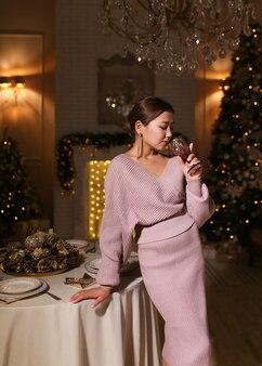 Una donna asiatica in un elegante abito di lusso sta con un bicchiere di vino in mano vicino all'albero