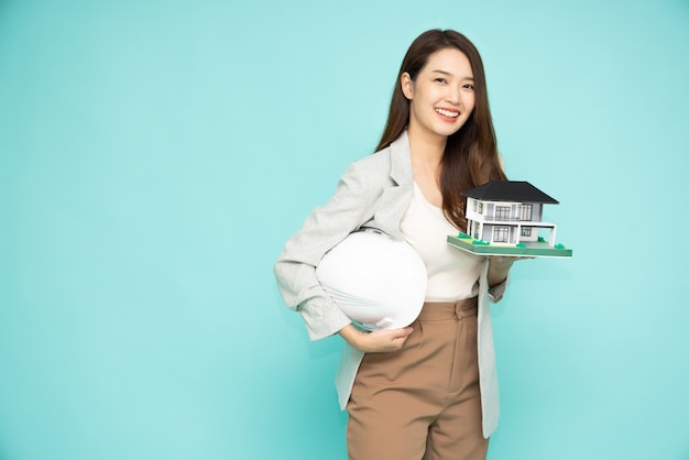 Donna asiatica o ingegnere in possesso di un casco bianco e modello di casa isolato su sfondo verde