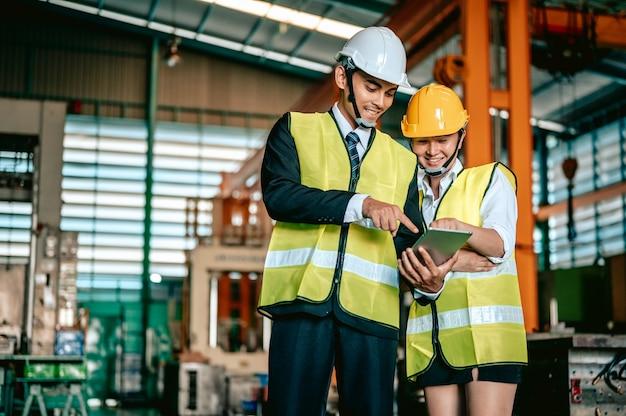 Industria dell'ingegnere donna asiatica che indossa l'elmetto protettivo e tiene la lista di controllo in piedi nell'area della macchina