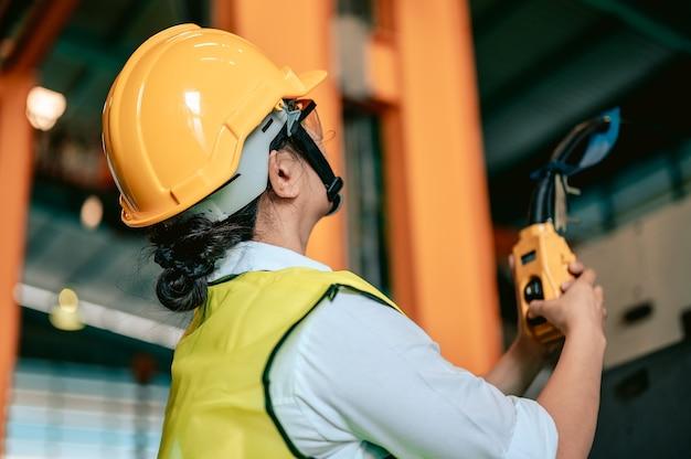 L'ingegnere asiatico utilizza il pannello di controllo remoto per sollevare o abbassare la gru del carrello elettrico