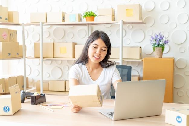 La donna asiatica si diverte mentre utilizza internet sul laptop e sul telefono in ufficio - vendi il concetto di acquisto online o online