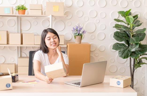 La donna asiatica si diverte mentre usa internet sul laptop e il telefono in ufficio - vendi il concetto di shopping online o online