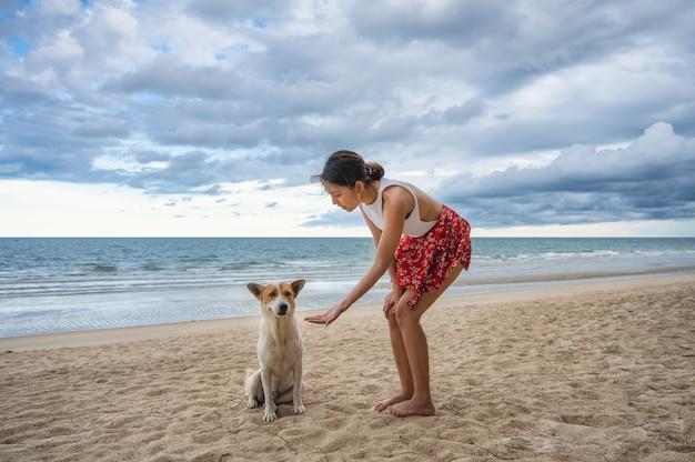 Donna asiatica che gode con dare la mano un cane sulla spiaggia nel mare tropicale in vacanza