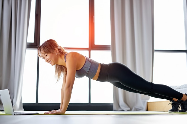 Donna asiatica che si esercita a casa, guardando il video tutorial sul laptop, allenamento sul pavimento. concetto di sport online