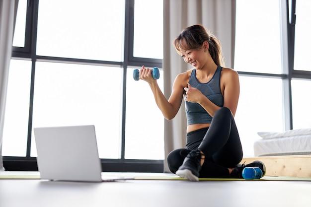 Donna asiatica che si esercita a casa, guardando il video tutorial sul laptop, allenamento con manubri sul pavimento. concetto di sport online