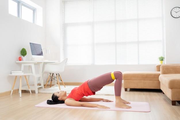 Donna asiatica che si esercita a casa su una stuoia di yoga.