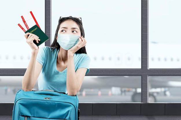 Donna asiatica nella maschera facciale con una valigia che tiene biglietto e passaporto al terminal dell'aeroporto. viaggiare nella nuova normalità