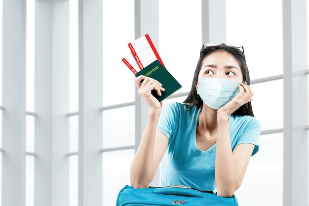 Donna asiatica nella maschera facciale con una valigia che tiene biglietto e passaporto in ospedale. controllo medico prima del viaggio