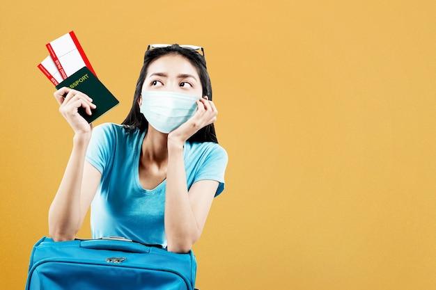 Donna asiatica nella maschera facciale con una valigia che tiene biglietto e passaporto. viaggiare nella nuova normalità