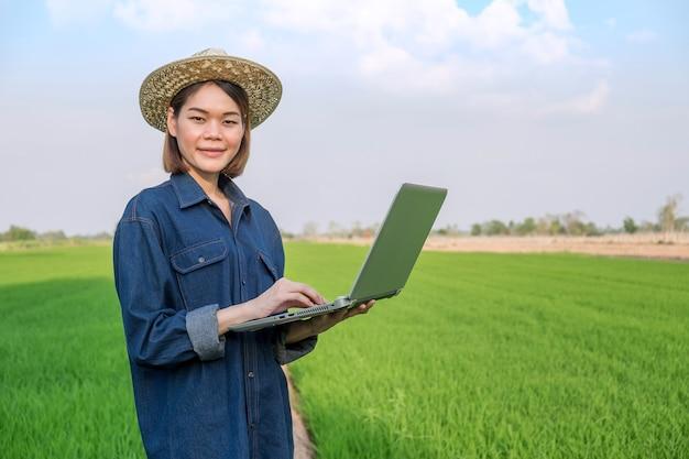 Contadina asiatica che indossa jeans in piedi e usa il computer portatile in un campo verde