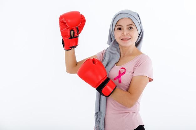 Una donna asiatica che combatte mostrando guantoni da boxe mese di consapevolezza del cancro al seno isolato su sfondo bianco vuoto spazio copia studio, assistenza sanitaria, concetto di medicina