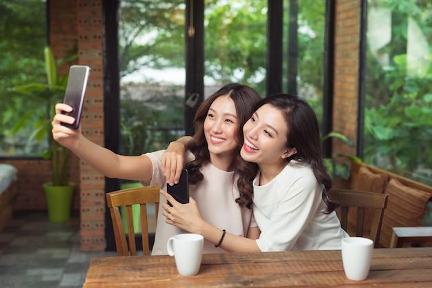 Amiche asiatiche che si abbracciano e fanno foto selfie insieme