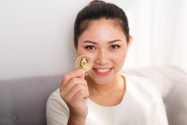La donna asiatica ottiene un sacco di soldi! donna attraente con tiene in mano bitcoin e guarda nella telecamera.