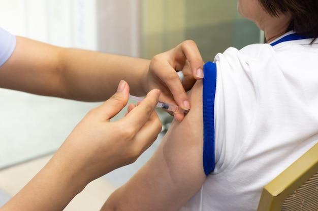 Donna asiatica che viene vaccinata