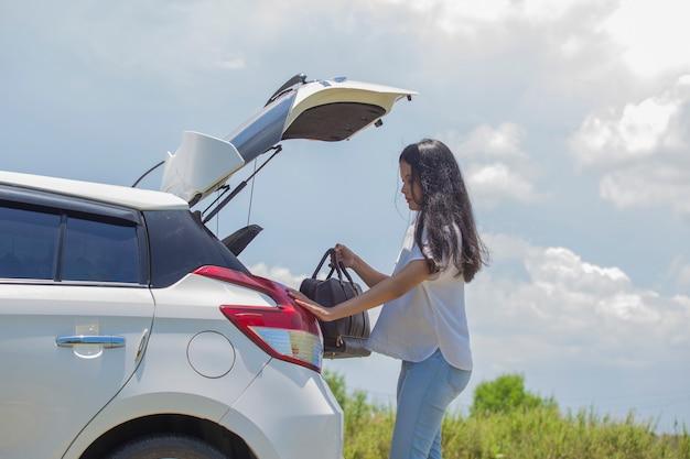 Donna asiatica che va in vacanza caricando il bagagliaio della macchina con valigie da viaggio