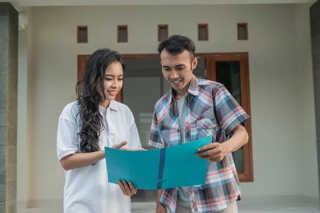 Gesto della mano della donna asiatica che chiacchiera sul certificato di casa con il promotore immobiliare mentre si tiene il certificato di casa davanti alla casa