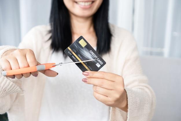 Mano della donna asiatica che tiene le forbici che tagliano la carta di credito finanziaria