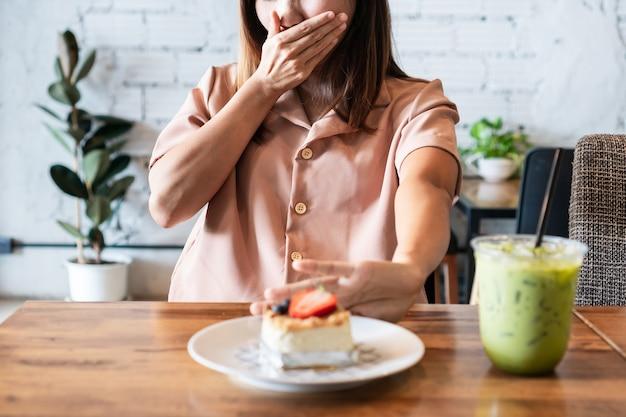 La mano asiatica della donna spinge fuori il cibo malsano. rifiutato cibo spazzatura, mangiare sano e concetto di dieta