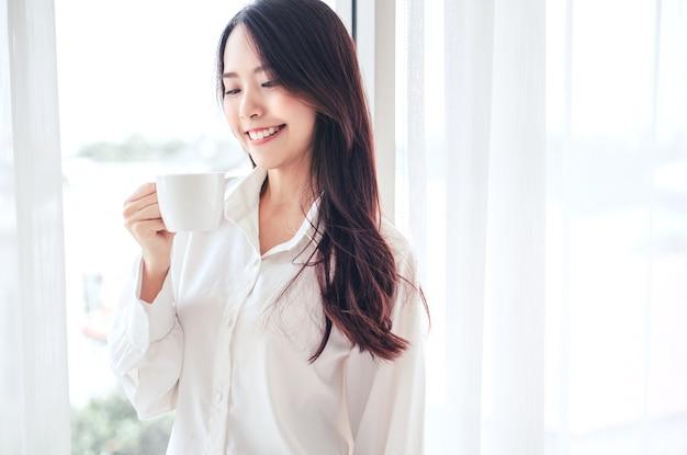 Mani della donna asiatica che tengono la tazza di caffè al mattino