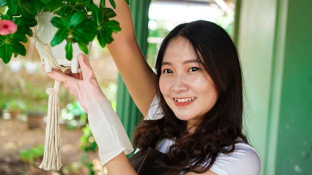 Le piante d'attaccatura della donna asiatica a casa fanno la bella decorazione