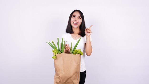 La donna asiatica ha una grande idea con un sacchetto di carta di verdure fresche con superficie bianca isolata