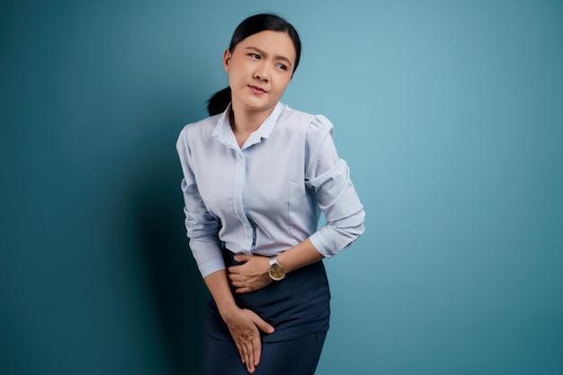 Donna asiatica che tiene le mani dolorose premendo il suo addome inferiore del cavallo
