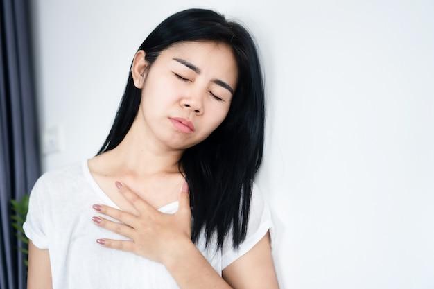 Donna asiatica che ha problemi con attacchi di asma e mancanza di respiro difficoltà a respirare
