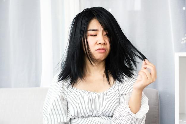 Donna asiatica che ha problemi con i capelli danneggiati, disordinati e sottili