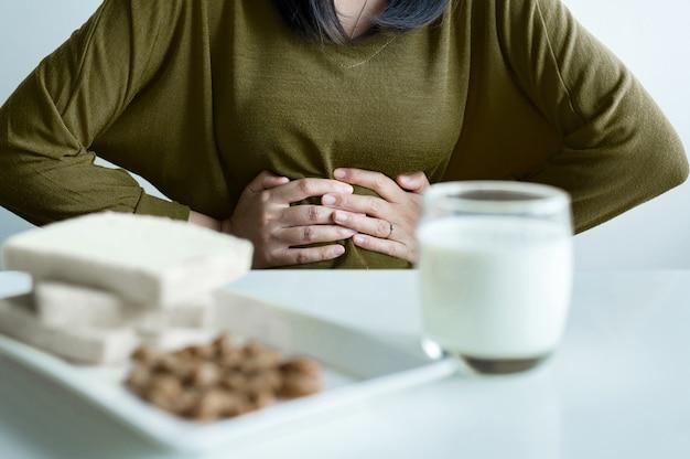 Donna asiatica che ha mal di stomaco con un bicchiere di latte