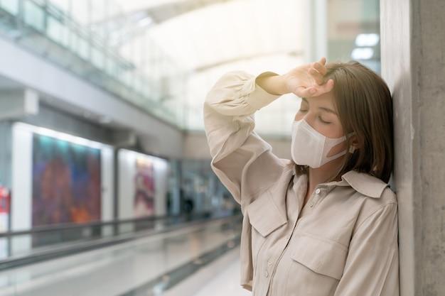 Maschere di indossare mal di testa donna asiatica al terminal dell'aeroporto nuova normale prevenzione delle malattie covid
