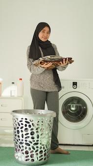 La donna asiatica in hijab porta vestiti che sono stati piegati ordinatamente a casa