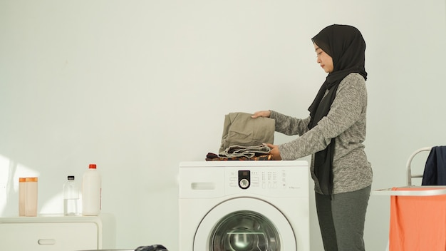 La donna asiatica in hijab piega i vestiti lavati a casa