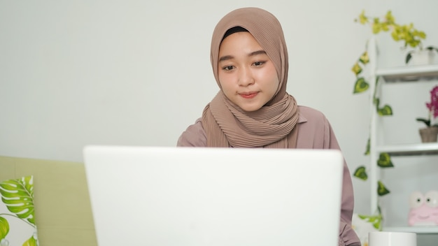 Donna asiatica in hijab che guarda lo schermo del suo laptop a casa