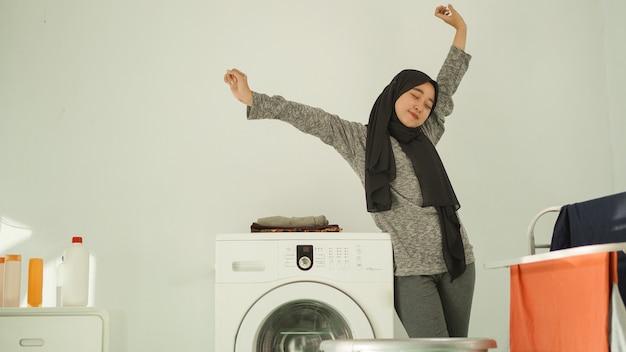 La donna asiatica in hijab si rilassa dopo aver lavato i vestiti a casa