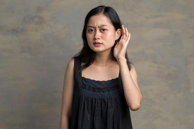 La donna asiatica tiene la sua mano vicino al suo orecchio e ascolta