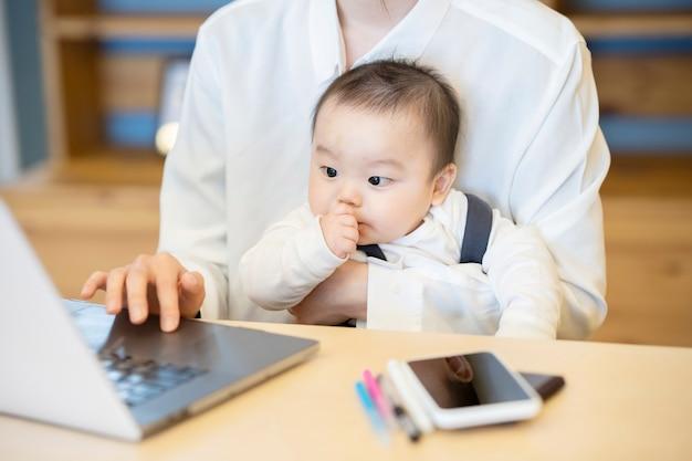 Donna asiatica che tiene un bambino e fa funzionare un computer portatile all'interno