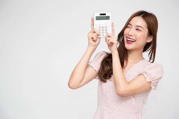 Calcolatrice della holding della donna asiatica isolata sul muro bianco,