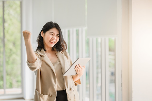Donna asiatica che tiene compressa digitale e che alza il suo braccio su