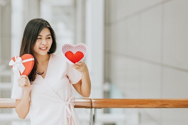 Contenitore di regalo asiatico della tenuta della donna con cuore rosso