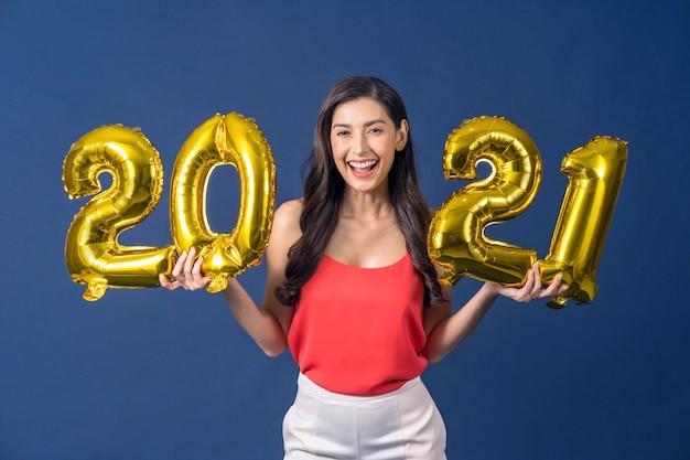 Donna asiatica che tiene palloncini color oro per festeggiare buon natale e felice anno nuovo