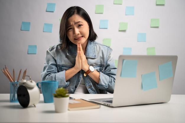 Donna asiatica che si tiene per mano in preghiera guardando la fotocamera e lavorando su un computer portatile in ufficio a casa. . lavoro da casa. concetto di prevenzione coronavirus covid-19.