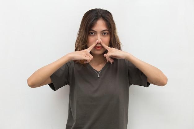 Donna asiatica che tiene il naso a causa di un cattivo odore