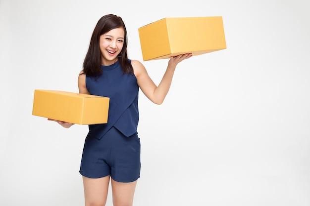 Donna asiatica che tiene la cassetta dei pacchi del pacchetto