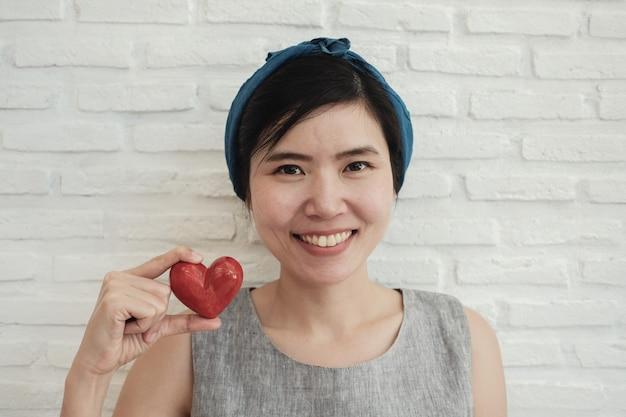 Donna asiatica che tiene cuore rosso, assicurazione sanitaria, carità di donazione