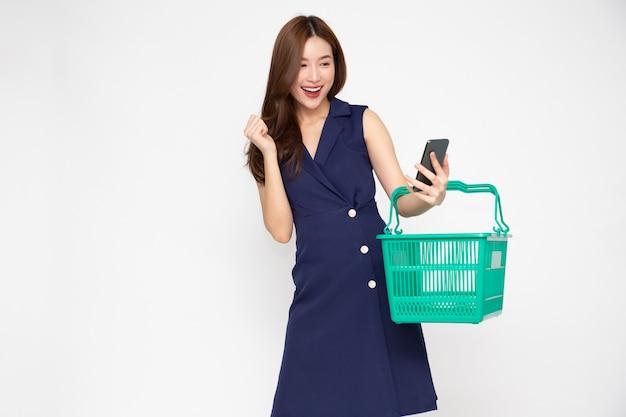 Donna asiatica che tiene cestino della spesa e mobile