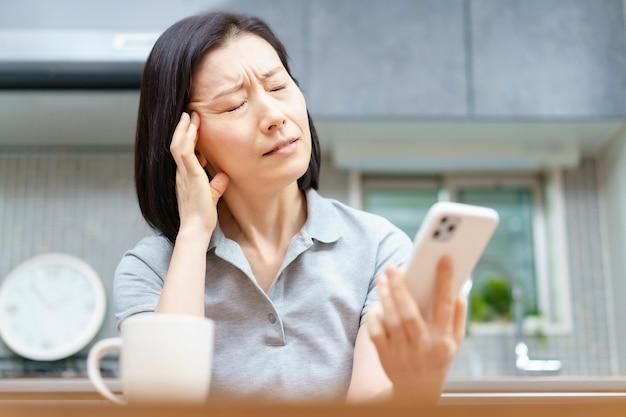 Donna asiatica che tiene uno smartphone con uno sguardo stanco nella stanza