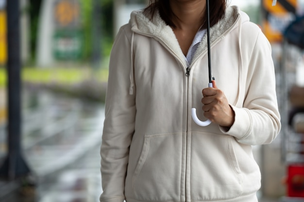 Donna asiatica che tiene l'ombrello durante l'attesa del taxi e in piedi sulla strada del marciapiede della città nel giorno di pioggia.