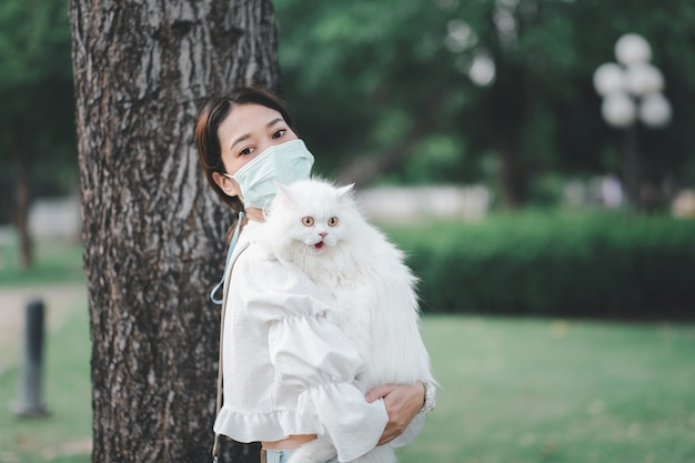 Donna asiatica che tiene un gatto bianco in un parco che indossa maschere anti virus durante l'epidemia di coronavirus